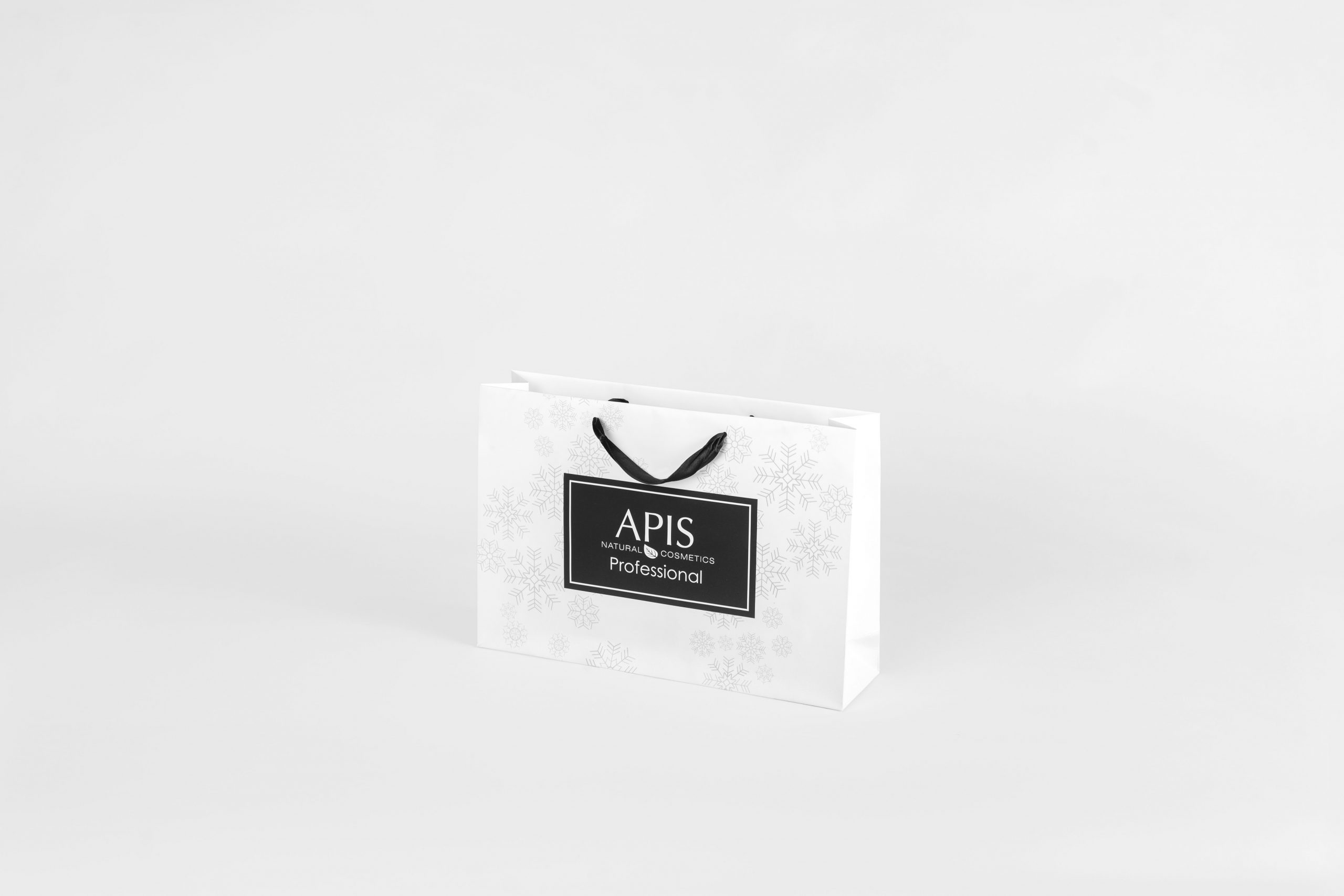 Niska biała torebka z czarnym logotypem i wstążką na kosmetyki